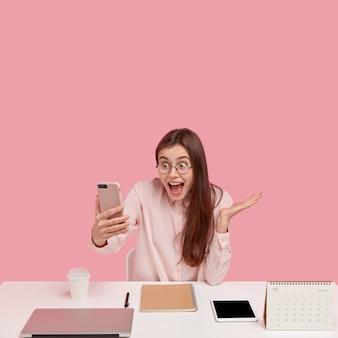 Concetto di tecnologia e comunicazione. donna allegra guarda nella fotocamera del telefono intelligente, attende la chiamata, indossa la camicia e gli occhiali