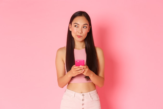 Technology, communication and online lifestyle concept. creative and thoughtful asian female smm, blogger thinking over new post, holding mobile phone, making choice what order in internet.