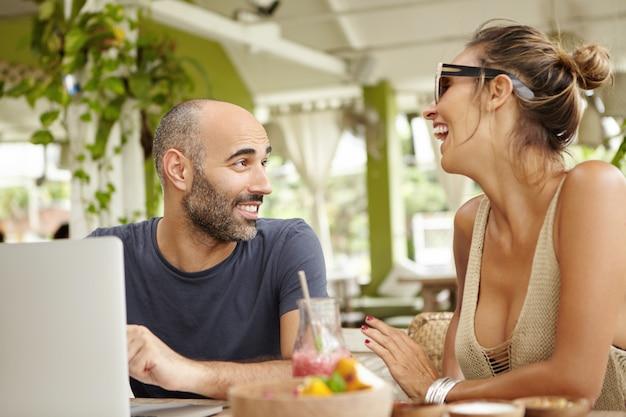 Tecnologia e comunicazione. due amici che hanno una conversazione vivace durante il pranzo.