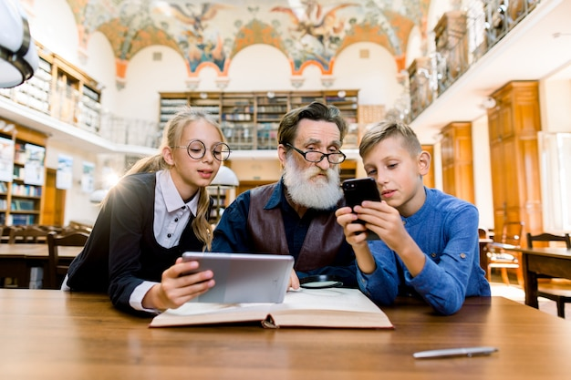 Technology, computer versus traditional print books concept. grandfather and grandchildren are sitting at the table in library.