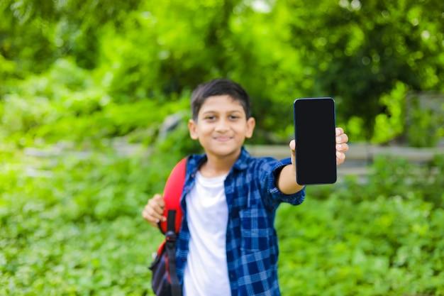 기술 개념 : 귀여운 인도 작은 학교 소년 가방을 들고 스마트 폰을 보여주는
