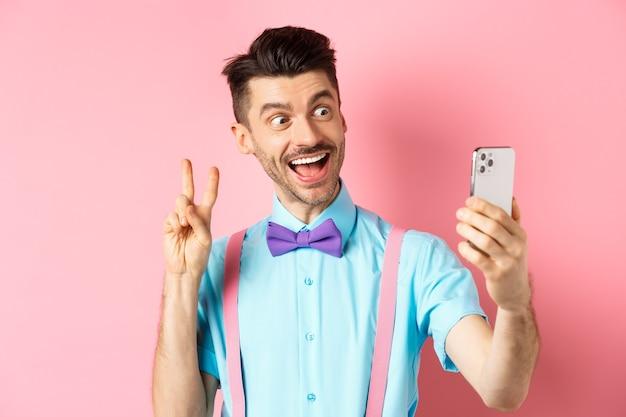 技術コンセプト。口ひげと蝶ネクタイを持った面白い男がスマートフォンで自分撮りをし、ピースサインを見せて、ピンクのモバイルカメラで笑っています。