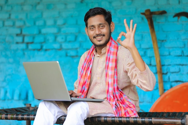 Technology concept : indian farmer using laptop at home.