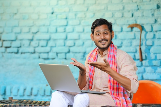 Technology concept : indian farmer using laptop at home