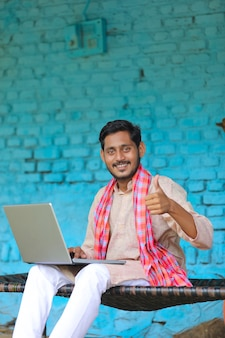 Technology concept : indian farmer using laptop and showing thumps up at home