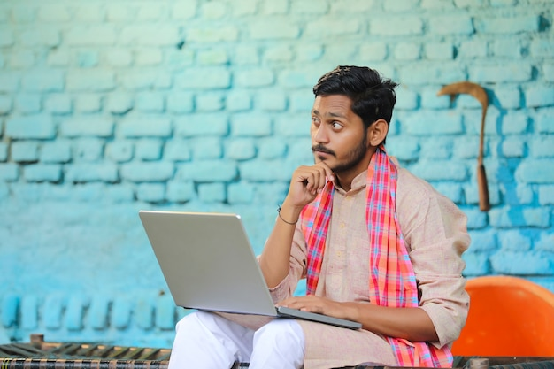 Technology concept : indian farmer using laptop and thinking at home