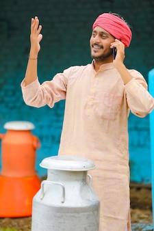 技術コンセプト:スマートフォンで話しているインドのミルク男。
