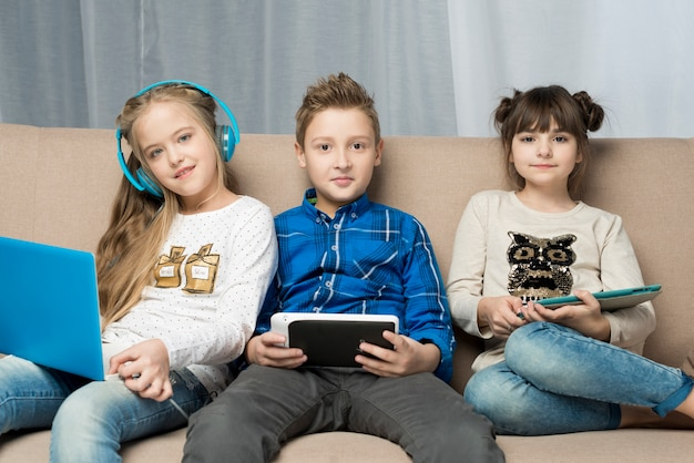 Technology concept with happy kids on couch