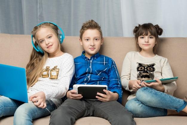 소파에 행복한 아이들과 기술 개념