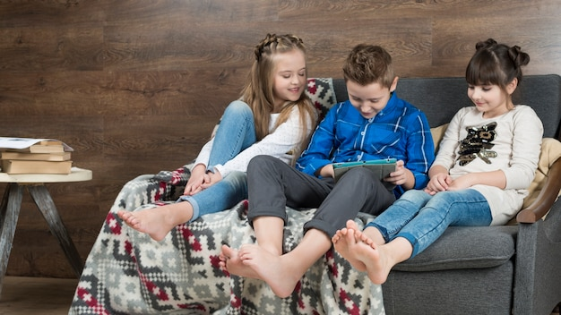 Technology concept with kids on sofa
