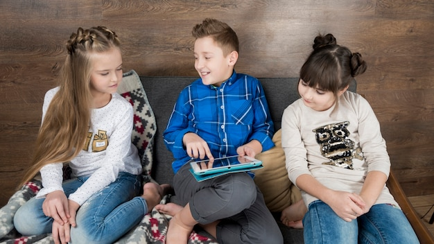 Technology concept with three kids on couch