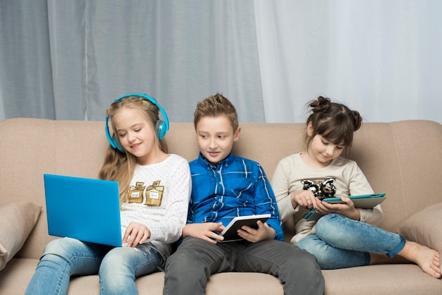 Technology concept with three kids on sofa