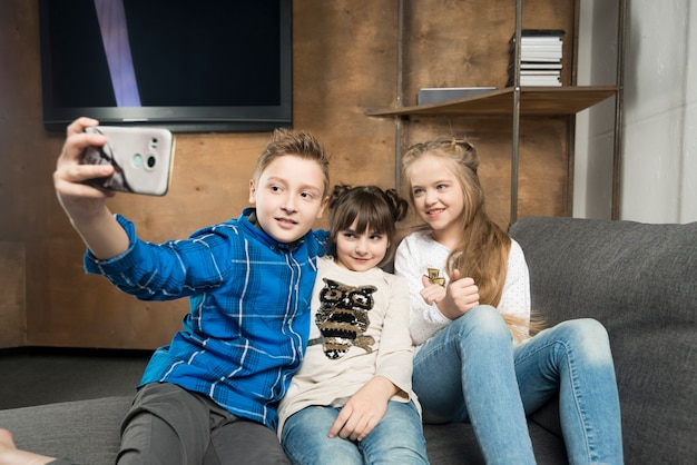 Concetto di tecnologia con tre bambini che assumono selfie