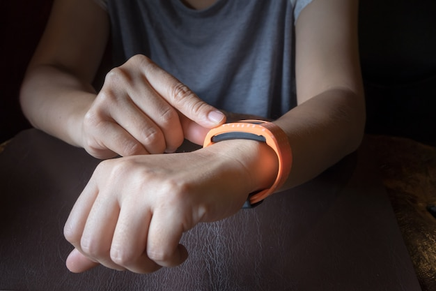 Technology concept. woman uses her smart watch / fitness tracker. photography in low key.
