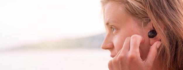 기술 개념입니다. 무선 이어폰을 사용하는 여성, 배경의 해변, 배너