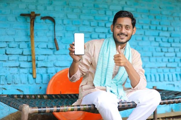 技術コンセプト:自宅でスマートフォンを見せている若いインドの農夫