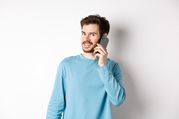 Technology concept. young male model talking on mobile phone, calling someone on smartphone and smiling, standing over white background.