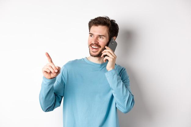 Концепция технологии. молодой человек разговаривает по мобильному телефону и указывая влево, имея вызов на смартфон, стоя на белом фоне.