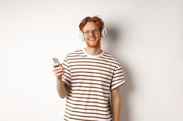 Концепция технологии. молодой человек с рыжими волосами и бородой слушает музыку в наушниках и с помощью смартфона, улыбаясь в камеру, на белом фоне.
