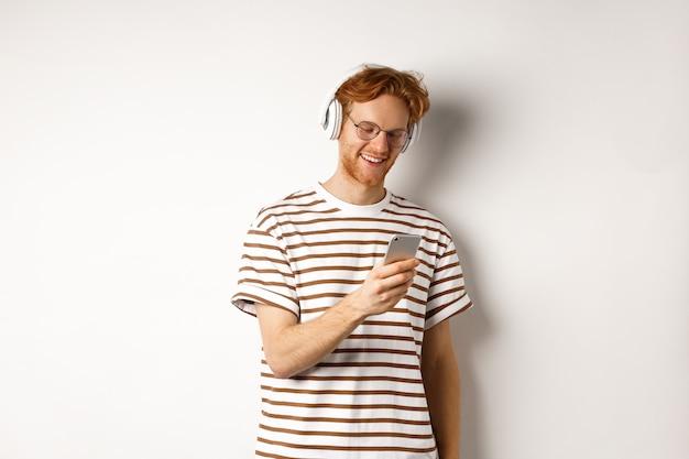 Концепция технологии. битник молодой рыжий в очках, слушать музыку в головные уборы, читать сообщение на смартфоне, на белом фоне.