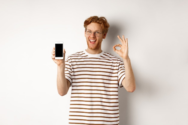 Technology and e-commerce concept. young man with red hair showing okay sign and blank smartphone screen, praising awesome app, standing over white background.