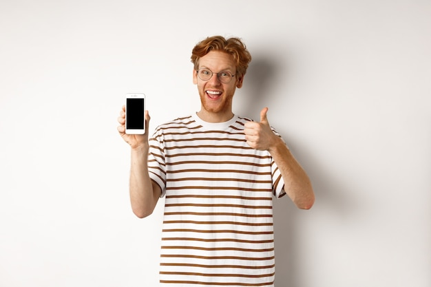 Technology and e-commerce concept. young man with red hair showing thumbs-up and blank smartphone screen, recommending app, white background.