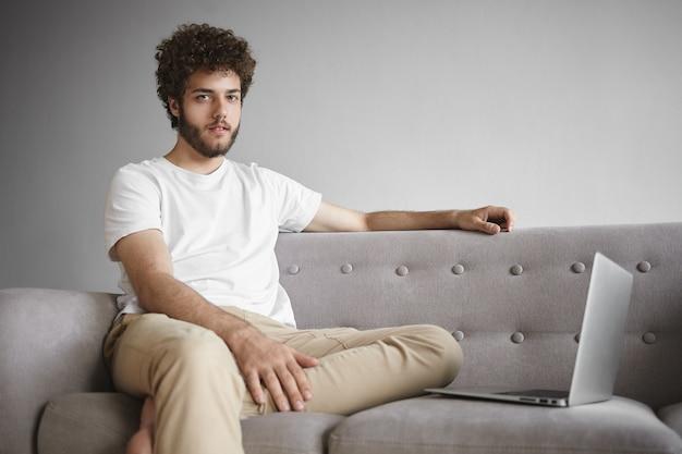 テクノロジー、電子ガジェット、コミュニケーションのコンセプト。スタイリッシュな若い男は、ワイヤレスインターネット接続を使用して、開いたポータブルコンピュータの前のソファに座って厚いひげとウェーブのかかった髪を羽ばたき