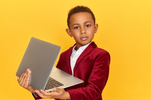 テクノロジー、電子ガジェット、デバイスのコンセプト。ワイヤレス高速インターネット接続を使用して、彼の手にラップトップで隔離されたポーズをとる自信を持って暗い肌の小さな男の子のスタジオ画像