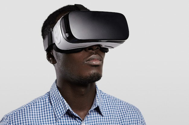 Technology, entertainment, gaming, cyberspace and people concept. serious dark-skinned player wearing checkered shirt and big modern 3-d glasses.