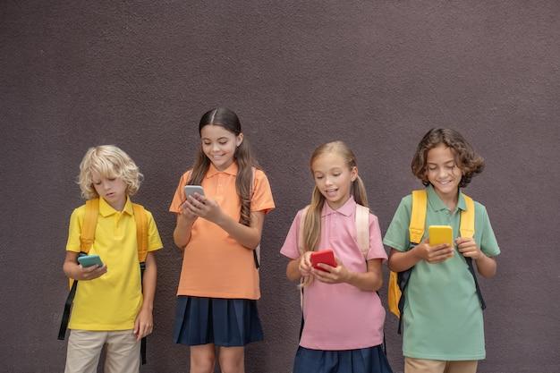 技術。スマートフォンでオンラインゲームをしている4人の子供