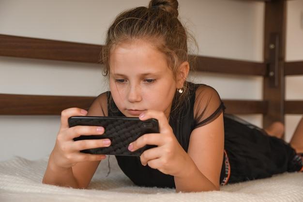 テクノロジー、自由時間、コミュニケーションの概念。ナイトウェアに身を包んだ陽気なティーンエイジャーは、オンラインチャット、ネットワーキングに携帯電話を使用し、テキストメッセージを受信し、ベッドに横たわっています