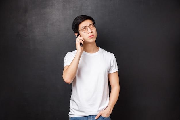 Концепция технологии, гаджеты и люди. портрет вдумчивого молодого азиатского парня, обдумывающего вопрос, вызывающего друга, говорящего по телефону, держащего смартфон и отводящего взгляд, размышляющего над ответом
