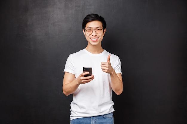 技術、ガジェット、人々の概念。携帯電話アプリケーション、配信サービス、またはインターネットストアを使用して満足しているハンサムなアジア人、承認として親指を立て、アプリを推奨