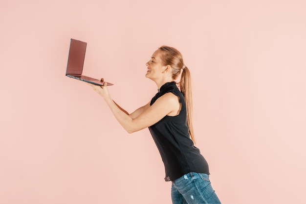 Technology and gadgets. remote work on outsourcing. a girl holds a laptop in her hands.