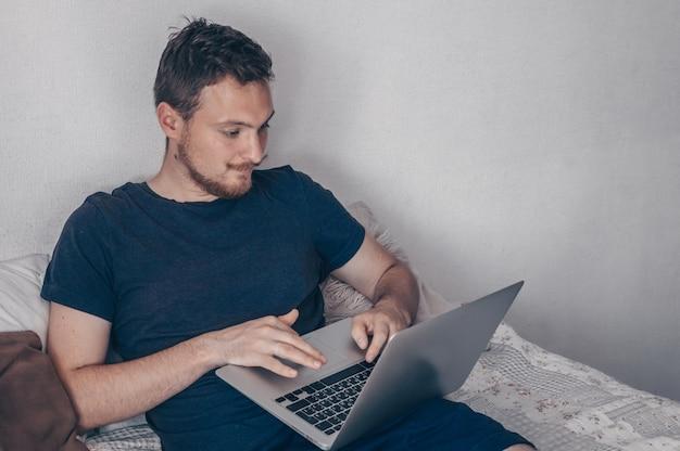 Концепция технологии, дома и образа жизни - закрыть человека, работающего с портативным компьютером и сидящего на диване у себя дома. молодой человек с помощью своего ноутбука с улыбкой, сидя на кровати дома