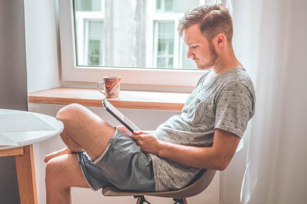 Технология, дом - концепция образа жизни крупным планом человека, работающего с планшетным компьютером и сидящего на стуле у себя дома