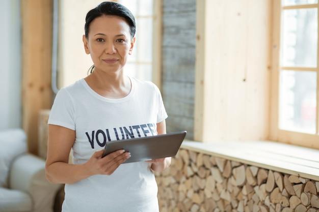 자원 봉사 기술. 초점을 맞춘 잠겨있는 여성 자원 봉사자 흐린 배경에 서서 카메라를 응시하는 동안 태블릿을 들고
