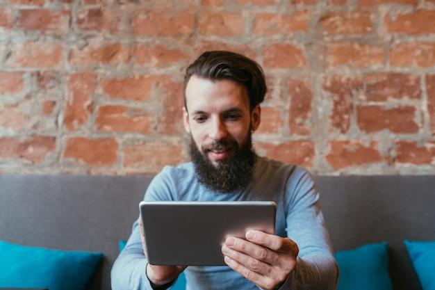 技術革新と開発。データを入力するためにセンサーのタッチスクリーンを使用してタブレットで入力する男性。