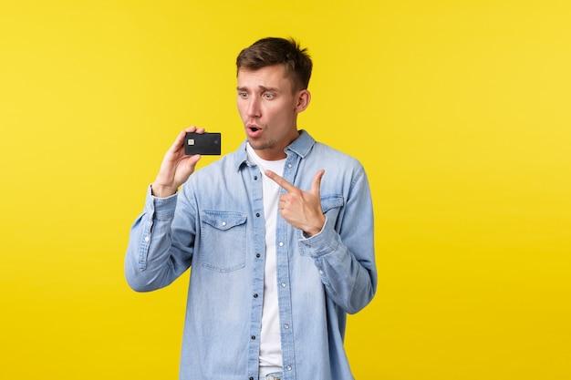 Tecnologia, stile di vita e concetto di pubblicità. eccitato e impressionato bel ragazzo che indica e guarda la carta di credito affascinato da nuove funzionalità o offerte promozionali speciali, sfondo giallo.