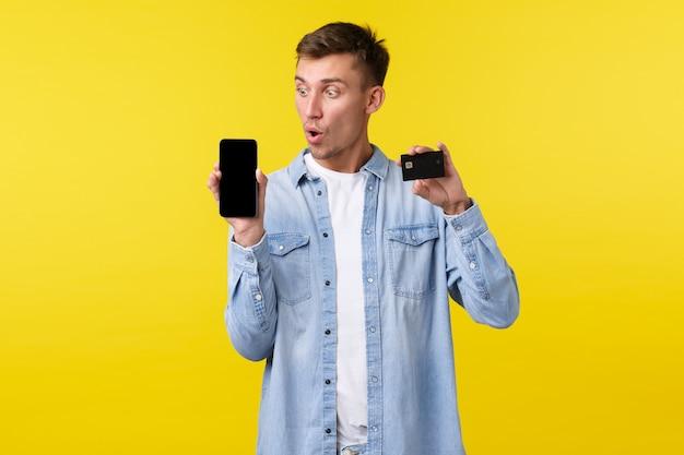 Tecnologia, stile di vita e concetto di pubblicità. ragazzo biondo impressionato e stupito che dice wow mentre guarda lo schermo del telefono cellulare, mostra il display dello smartphone e la carta di credito, fa ordine.
