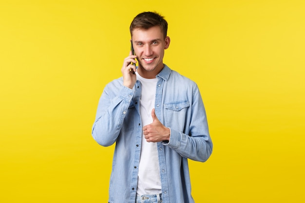Technology, lifestyle and advertisement concept. pleased good-looking man talking on phone, assure everything going well, showing thumbs-up to encourage you all good, making agreement while calling