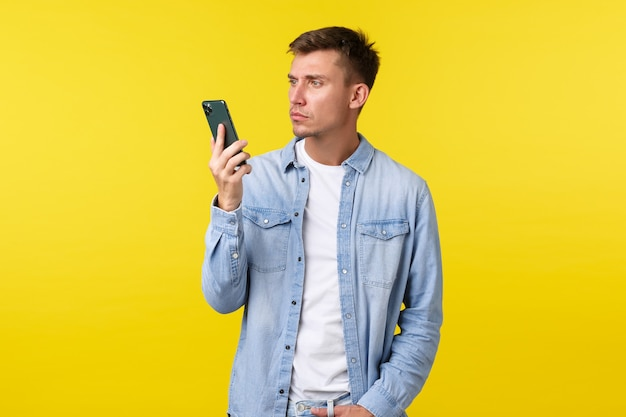 기술, 라이프 스타일 및 광고 개념입니다. 짜증나고 좌절한 청년은 갑자기 끝난 대화에 어리둥절해하며 노란색 배경 위에 서 있는 초조한 휴대폰을 바라보고 있습니다.