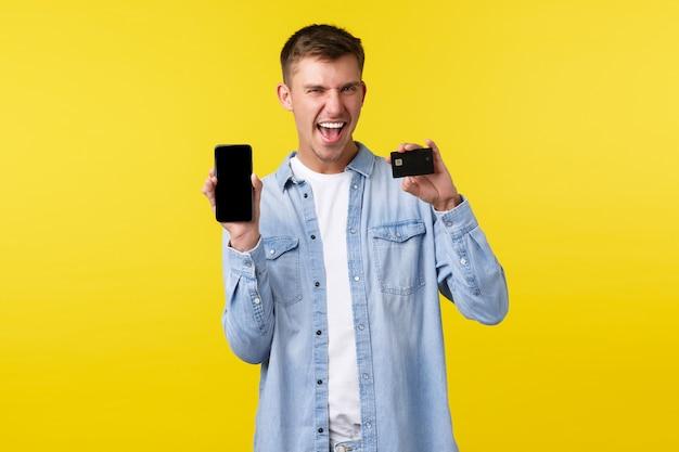 テクノロジー、ライフスタイル、広告のコンセプト。クレジットカードと携帯電話を見せて、笑顔で「はい」と言って、熱狂的な幸せな金髪の男は、オンラインで販売されているクールなもの、黄色の背景を購入しました。