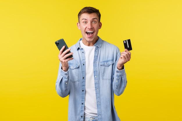Концепция технологии, образа жизни и рекламы. взволнованный и удивленный счастливый белокурый мужчина, подняв руки вверх, показывает кредитную карту и приложение для мобильного телефона, сделал заказ онлайн на специальной распродаже.