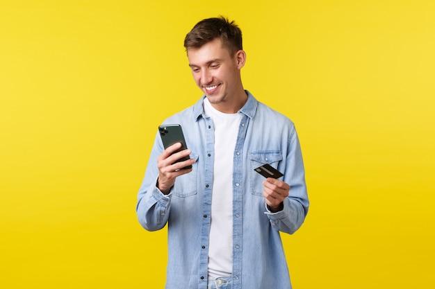 Концепция технологии, образа жизни и рекламы. красивый улыбающийся счастливый белокурый парень, глядя на приложение для мобильного телефона, оплачивая заказ или доставку на сайте покупок, держите кредитную карту, желтый фон.