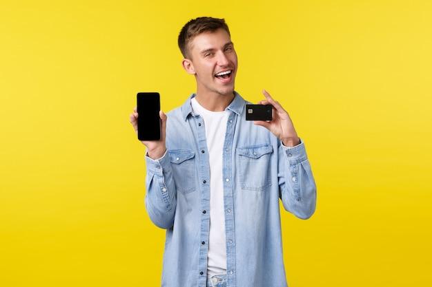 Концепция технологии, образа жизни и рекламы. красивый улыбающийся мужчина представляет новую функцию в приложении, показывая кредитную карту и экран мобильного телефона с довольным лицом, желтым фоном.