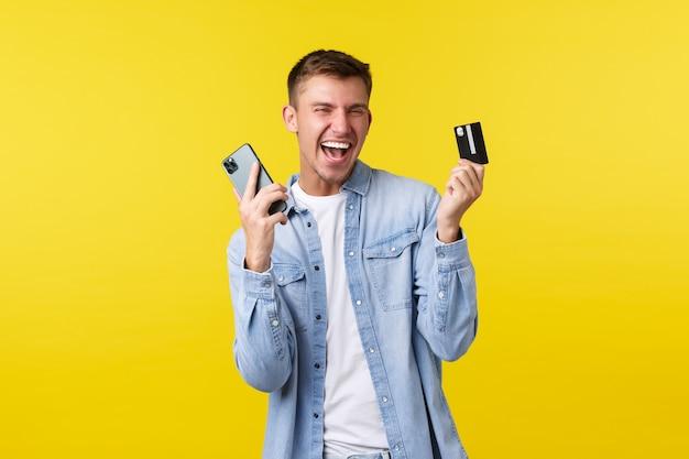Концепция технологии, образа жизни и рекламы. счастливый радостный красивый мужчина танцует, когда совершил потрясающую покупку в интернете, показывая кредитную карту и мобильный телефон как радость, желтый фон.