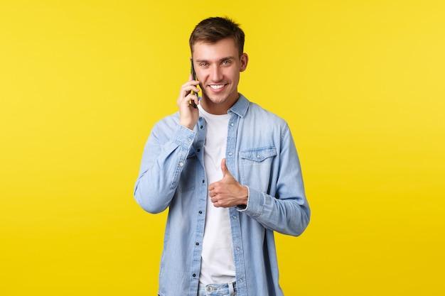 テクノロジー、ライフスタイル、広告のコンセプト。電話で話しているイケメンを喜ばせ、すべてが順調に進んでいることを確認し、親指を立ててすべての人を励まし、電話をかけながら同意します
