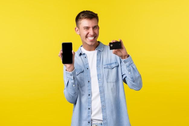 テクノロジー、ライフスタイル、広告のコンセプト。クレジットカードと携帯電話を見せて、買い物のためのアプリをお勧めし、黄色の背景に立って幸せな金髪の男を喜ばせます。コピースペース