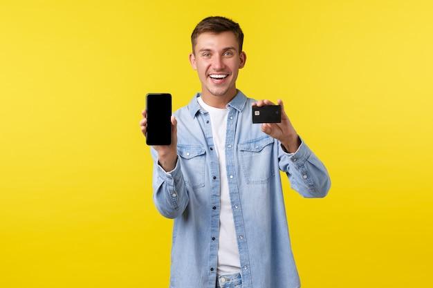 Концепция технологии, образа жизни и рекламы. улыбающийся красивый мужчина-покупатель, студент, показывающий супер крутое приложение, дисплей смартфона и кредитная карта, рекомендующий магазин, желтый фон.